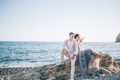 Beautiful couple bride and groom near the sea sitting back to back and smiling royalty free stock photos