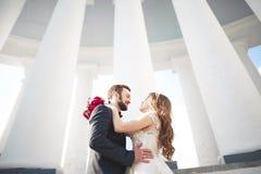 Beautiful couple, bride and groom posing near big white column Royalty Free Stock Photo
