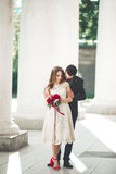 Beautiful couple, bride and groom posing near big white column Stock Images