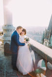 Beautiful couple, bride and groom posing on old balcony with column, cityscape background Royalty Free Stock Image
