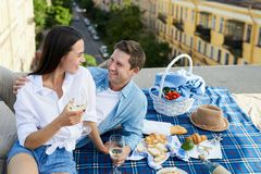 Beautiful couple chatting and laughing on roof. Smiling excited beautiful young couple chatting and laughing on roof while sitting on blanket with food and royalty free stock images
