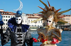 Beautiful couple in colorful costumes and masks, view on the Grand Canal. Stock Image
