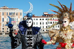 Beautiful couple in colorful costumes and masks, view on the Grand Canal. Stock Photography