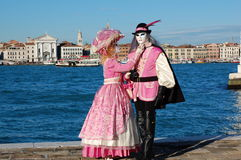 Beautiful couple in colorful costumes and masks, view on Piazza San Marco Royalty Free Stock Images