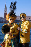 Beautiful couple in colorful costumes and masks, view on Piazza San Marco Stock Photos