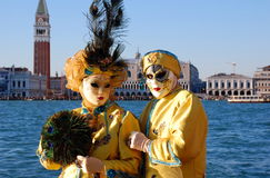 Beautiful couple in colorful costumes and masks, view on Piazza San Marco Royalty Free Stock Photos