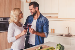 Beautiful couple cooking. Beautiful couple is drinking wine, talking and smiling while cooking in kitchen stock images