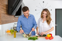 Beautiful couple cooking healthy food together. Beautiful couple standing and cooking healthy food together on the kitchen Stock Photography