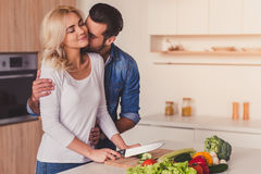 Beautiful couple cooking. In kitchen. Guy is kissing his girlfriend while she is cutting vegetables, both are smiling Stock Images