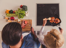 Beautiful couple cooking. Top view of beautiful young couple cooking together in kitchen Royalty Free Stock Photography