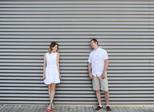 Beautiful couple costs at a motley wall. Royalty Free Stock Photography