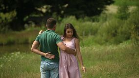 Beautiful couple dance in the field. the enjoy each other and smile. Summer weather. Romantic atmophere. slow motion. Beautiful couple dance in the field. the stock footage