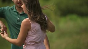 Beautiful couple dance in the field. the enjoy each other and smile. Summer weather. Romantic atmophere. slow motion. Beautiful couple dance in the field. the stock video footage