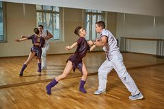 Beautiful couple dancing bachata in dance studio. Beautiful young couple dancing bachata in dance studio mirror room. women in purple dress and men in white suit royalty free stock image