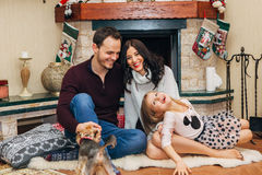 Beautiful couple with daughter in love near fireplace Stock Photo