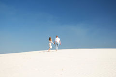 A beautiful couple in the distance among the white boundless sands Royalty Free Stock Photo