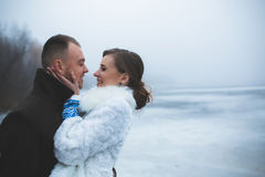 Beautiful couple on the dock in the winter fog. Stock Photos