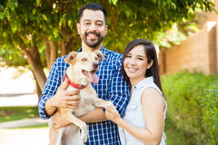 Beautiful couple with a dog. Attractive young Hispanic couple hanging out at a park with their dog and looking like a happy family Stock Image