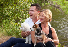Beautiful couple with dogs at lake Stock Photos