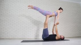Beautiful couple doing acro yoga in studio stock photo
