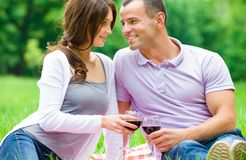 Beautiful couple drinks wine in park Royalty Free Stock Photography