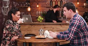 Beautiful couple eating croissants and drinking coffee in stylish coffee shop restaurant pub