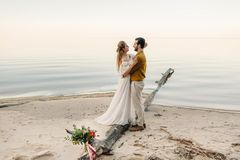 A beautiful couple is embracing on the sea background. Moment before the kiss. Romantic date on the beach. Wedding Royalty Free Stock Photography