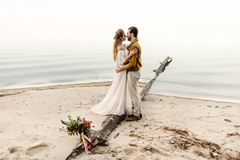 A beautiful couple is embracing on the sea background. Moment before the kiss. Romantic date on the beach. Wedding. Artwork, soft focus Royalty Free Stock Photos