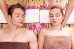 Beautiful couple enjoying head massage. Royalty Free Stock Image