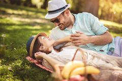 Couple enjoying picnic time outdoor reading book. Beautiful couple enjoying picnic time outdoor reading book royalty free stock photography