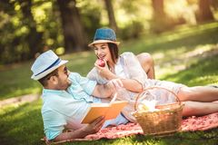 Couple enjoying picnic time outdoor reading book. Beautiful couple enjoying picnic time outdoor reading book royalty free stock images
