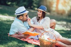 Couple enjoying picnic time outdoor reading book. Beautiful couple enjoying picnic time outdoor reading book stock photos