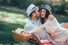 Couple enjoying picnic time outdoor reading book. Beautiful couple enjoying picnic time outdoor reading book stock image
