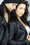 Beautiful couple fashion. Beautiful couple wearing a leather jacket over a grey background Stock Photo