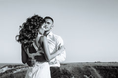 Beautiful couple in field, Lovers or newlywed posing on sunset with perfect sky. Black and white Royalty Free Stock Photo