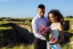 Beautiful couple in field, Lovers or newlywed posing on sunset with perfect sky. Real emotions royalty free stock photo