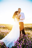 Beautiful couple in field, Lovers or newlywed posing on sunset with perfect sky. Real emotions stock photo
