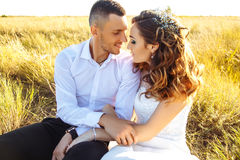 Beautiful couple in field, Lovers or newlywed posing on sunset with perfect sky. Real emotions stock photography