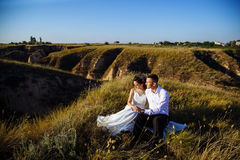 Beautiful couple in field, Lovers or newlywed posing on sunset with perfect sky. Real emotions stock image