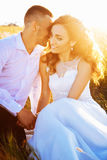 Beautiful couple in field, Lovers or newlywed posing on sunset with perfect sky Stock Photo