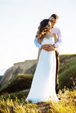 Beautiful couple in field, Lovers or newlywed posing on sunset with perfect sky Royalty Free Stock Images