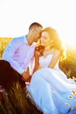 Beautiful couple in field, Lovers or newlywed posing on sunset with perfect sky Stock Image