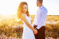 Beautiful couple in field, Lovers or newlywed posing on sunset with perfect sky Royalty Free Stock Photography