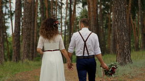 Beautiful couple go on a forest road. The groom holds one hand to the bride, the other hand a beautiful bouquet. The view from the stock video footage