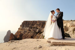 Beautiful couple. gorgeous bride in wedding dress posing with elegant groom on sea cost. Fashion outdoor photo of beautiful couple. gorgeous bride in wedding Royalty Free Stock Photo