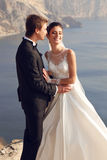 Beautiful couple. gorgeous bride in wedding dress posing with elegant groom on sea cost Stock Photo