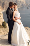 Beautiful couple. gorgeous bride in wedding dress posing with elegant groom on sea cost Royalty Free Stock Images