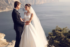 Beautiful couple. gorgeous bride in wedding dress posing with elegant groom on sea cost Royalty Free Stock Image