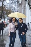 Beautiful couple, guy and his girlfriend dressed in casual clothes are running under the umbrella on the street in the royalty free stock image