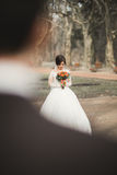 Beautiful couple of happy stylish newlyweds walking in the  park on their wedding day with bouquet Royalty Free Stock Photo